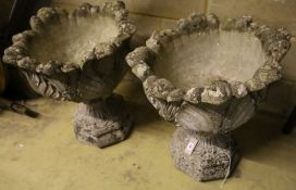 A pair of reconstituted stone leaf pattern garden urns, height 58cm