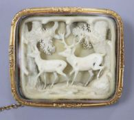 A 19th century Austro-German yellow metal framed brooch, inset with carved ivory forest scene