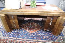 A French Art Deco rosewood desk in the manner of Paul Follot Height 74cm, width 185cm, depth 108cm.