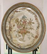 An early 19th century silkwork panel of flowers in a cornucopia, oval 50 x 42cmCONDITION: Embroidery