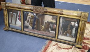 A Regency mahogany gilt-framed overmantel mirror centred by a military trophy, 160 x 60cm