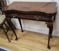 A George I red walnut serpentine top card table, with dished corners, frieze drawer and slender