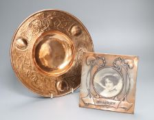An Art Nouveau copper dish, diameter 26cm and an Art Nouveau oxidised copper photo frame, 'Dinna
