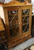 A glazed pine two door bookcase, width 112cm depth 26m height 150cm