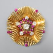 A late 1950's 18ct gold, ruby and diamond cluster set stylised flower head pendant brooch, 45mm,