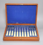 A Victorian set of twelve plated and engraved fish knives and forks, with carved ivory handles,