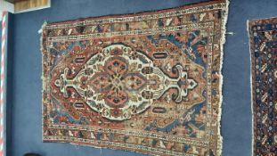 A Heriz brick red ground rug, 192 x 135cm