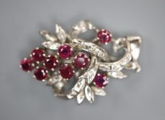 A modern 18k white metal, ruby and diamond chip set scroll pendant, 30mm, gross 5.6 grams.CONDITION: