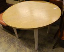 A contemporary circular oak dining table, 110cm diameter