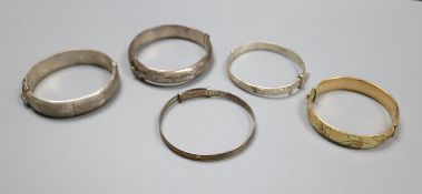 Four assorted silver bangles and a gold plated bangle.