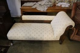 A late 19th century chaise longue with carved oak frame on turned legs and castors