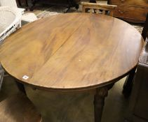 An early 20th century mahogany circular extending dining table, 180cm extended (two spare leaves)