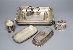 A pair of silver plated entree dishes with covers and handles, a plated butter dish, two condiments,