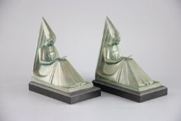 Max le Verrier. A pair of Art Deco patinated bronze bookends, modelled as seated medieval maidens,