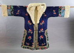 A Chinese blue silk multicoloured embroidered Chinese winter robe, early 20th century, with a