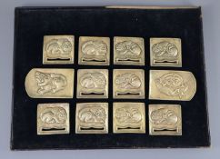 A set of twelve Chinese gilt bronze belt plaques, Tang-Liao dynasty or later, each cast in relief