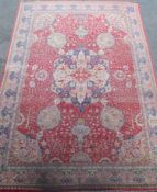 A Kirman carpet, the claret field with overall flowering shrub and palmette design centred by an
