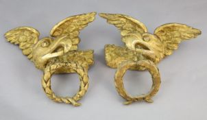 A pair of early 19th century carved giltwood and gesso wall appliqués, each modelled as a winged