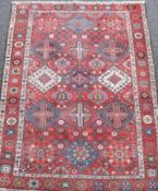 A Bakhtiari red ground carpet circa 1900, with field of geometric motifs and three row border,