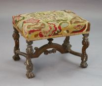 A late 17th century walnut dressing stool, with scroll carved legs, arched stretcher and fluted