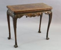A mid-18th century Irish carved walnut folding top card table, with scallop and scroll carved