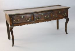 An early 18th century oak dresser base, fitted three long drawers with brass loop handles, on