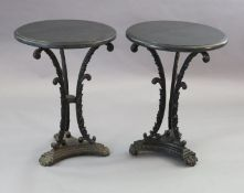 A pair of early Victorian cast iron occasional tables, with later circular black granite tops,