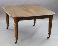 A Victorian mahogany extending dining table, with rounded rectangular top and three spare leaves, on