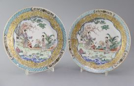 A fine pair of Chinese famille rose plates, Yongzheng period, each painted with two ladies in a