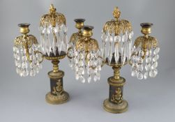 A pair of Regency bronze and ormolu lustre candelabra, with foliate scroll branches, hung with spear