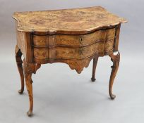 An 18th century Dutch and walnut marquetry lowboy, decorated with flowers in an urn, masks, birds,