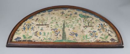 A late 17th century silk and bead work arched panel, with central tree, birds, butterflies, exotic