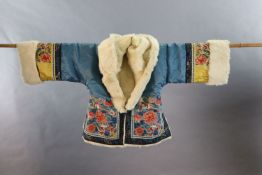 A Chinese embroidered silk winter jacket, late 19th/early 20th century, with white fur lining,