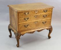 A Georgian style crossbanded walnut chest of three graduated long drawers, with quarter veneered