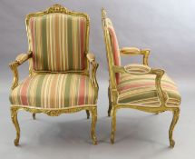 A pair of French gilt beech fauteuils, with moulded foliate scroll carved frames and cabriole