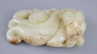A Chinese pale celadon jade figure of a chilong, the figure with scrolling tail, the stone with