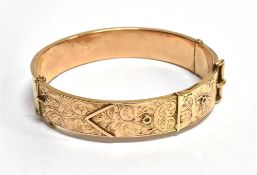 A HALLMARKED 9CT GOLD HINGED BANGLE in the form of a belt and buckle, engraved scroll decoration