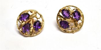 A PAIR OF THREE STONE AMETHYST SET 9CT GOLD EARRINGS the round stud earrings each set with three