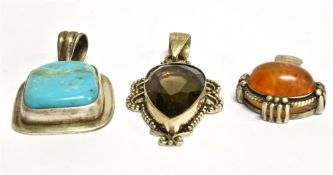 THREE SILVER STONE SET LARGE PENDANTS comprising a pear shaped smoky quartz, an oval clarified amber