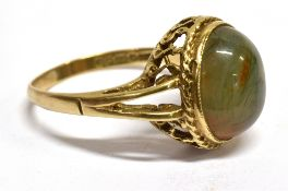 A MODERN MOSS AGATE SINGLE STONE 9CT GOLD DRESS RING The oval cabochon cut agate 12mm x 10mm, 9ct