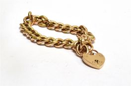 AN EDWARDIAN 9CT GOLD BRACELET WITH PADLOCK FASTENER the twisted curb links of hollow construction