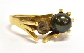 AN 18CT GOLD 1960'S DESIGN BLACK PEARL SET RING The two bead ring with one bead missing,