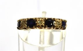 A 9CT GOLD SEVEN STONE HALF HOOP RING four round cut blue sapphires alternating with three small