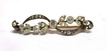 AN EDWARDIAN DIAMOND SET BAR BROOCH the garland style front comprising leaf and scroll design, rub