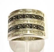 A BLACK AND WHITE DIAMOND SET SILVER BAND RING the front section comprising five rows of alternating