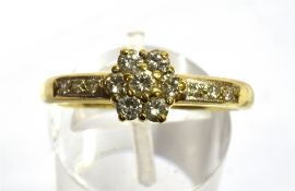 A DIAMOND FLOWER HEAD CLUSTER 18 CARAT GOLD RING the flower head cluster comprising seven round