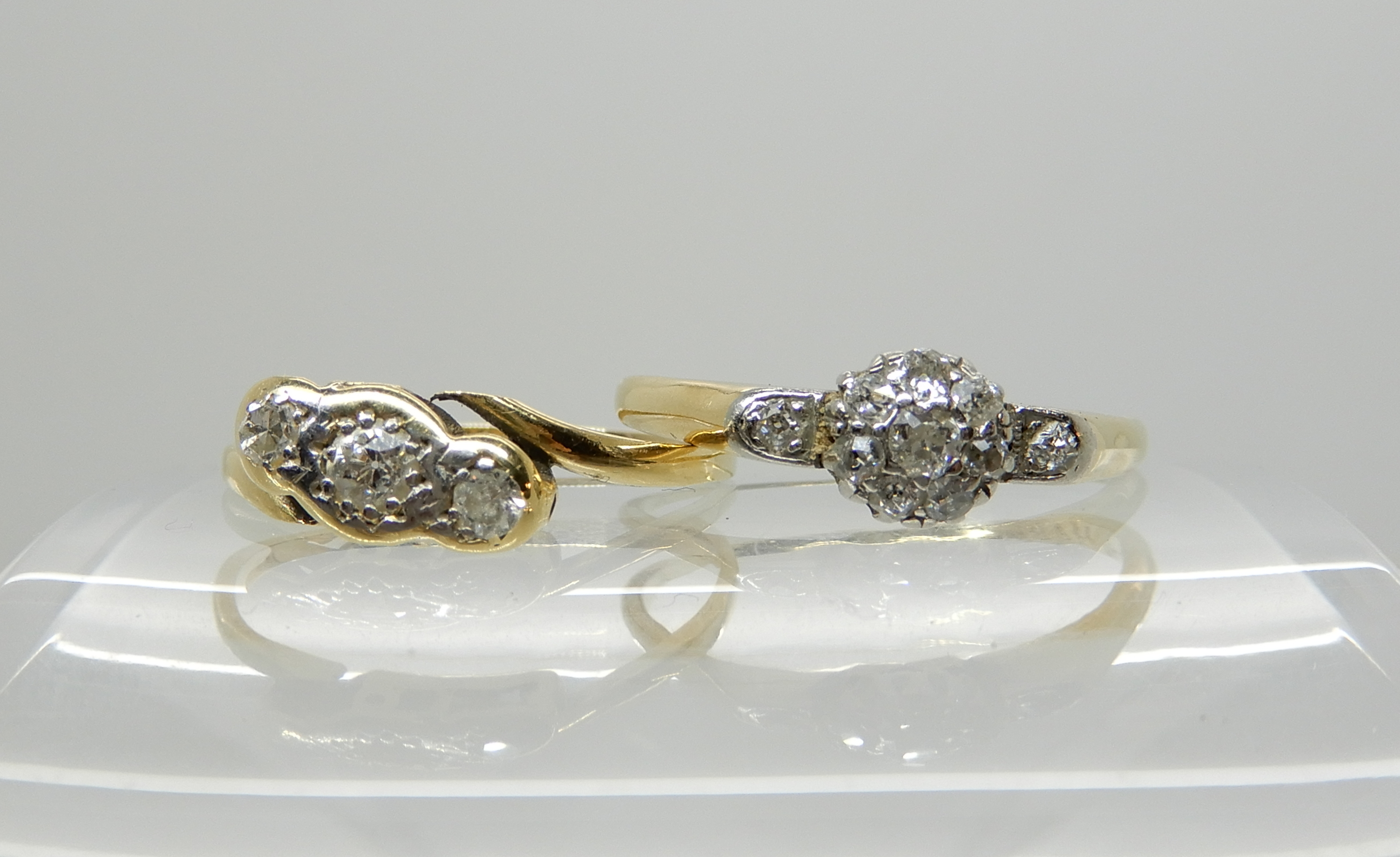Lot 39 - A bright yellow metal old cut diamond cluster ring size O1/2 and a three stone diamond ring size