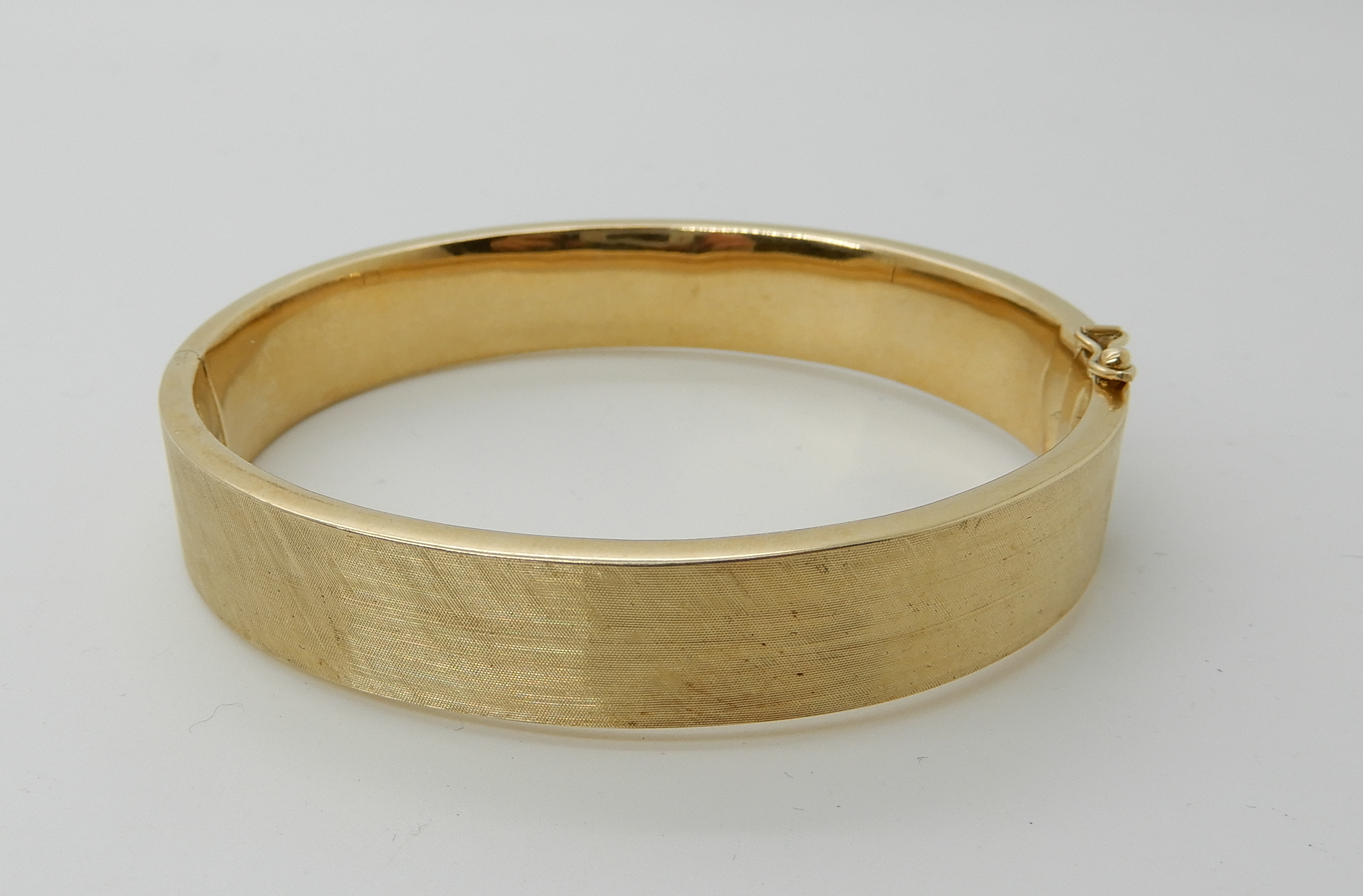 Lot 24 - A 14k gold brushed textured bangle, inner dimensions 6.3cm x 5.6cm, weight 25gms Condition Report: