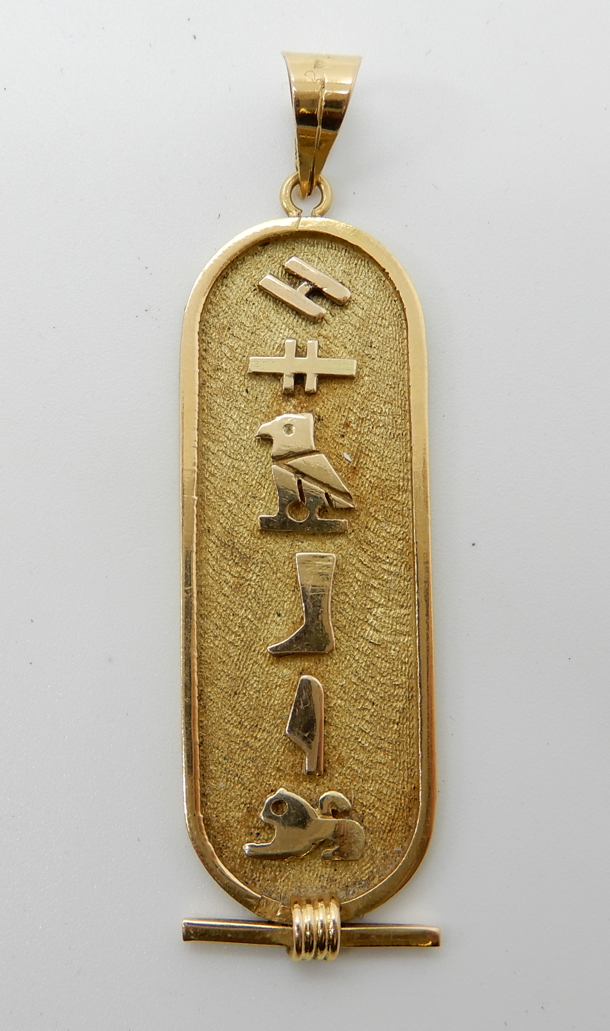 Lot 37 - A bright yellow metal Egyptian hieroglyph pendant with Arabic gold stamps, weight approx 4.7gms