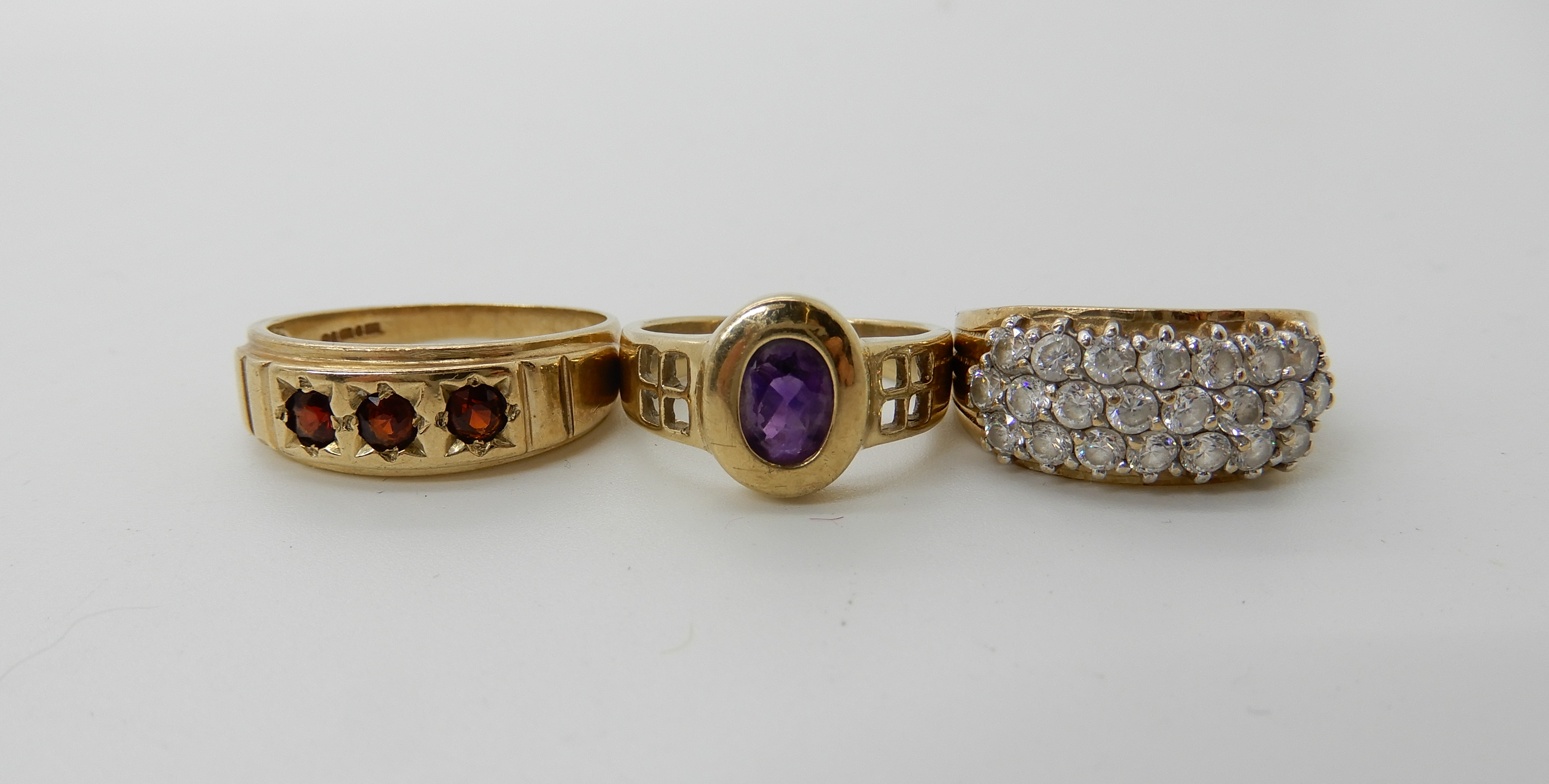 Lot 5 - A 9ct gold amethyst set Mackintosh style ring, size L, a 9ct garnet ring size T1/2 and a 9ct clear